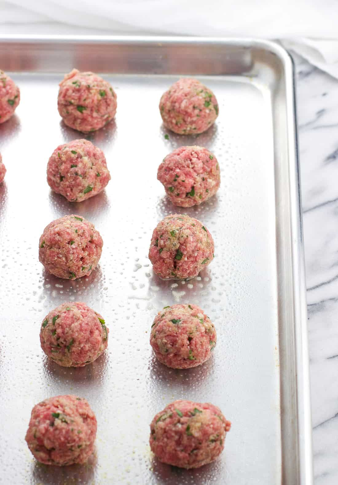Raw meatballs lined up on an aluminum baking sheet.