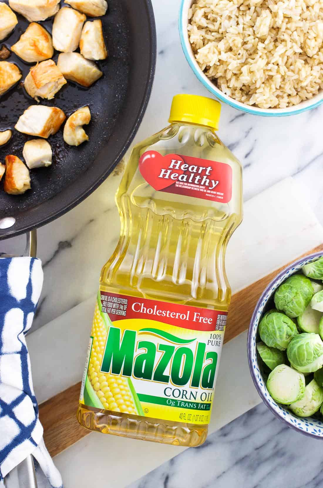 An overhead picture of a container of Mazola corn oil surrounded by a skillet of cooked chicken, a bowl of cooked brown rice, and a bowl of raw Brussels sprouts
