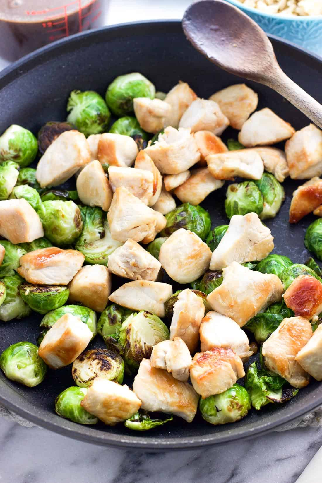 Cooked chicken and sauteed Brussels sprouts in a skillet next to a wooden spoon