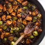 The chicken and Brussels sprouts stir fry in a skillet with a wooden spoon all ready to serve