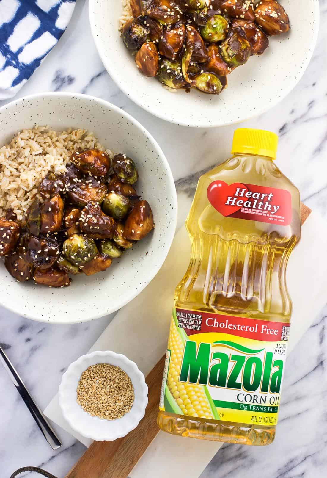 A bottle of Mazola corn oil next to two plates of chicken stir fry served with brown rice and a small bowl fo toasted sesame seeds