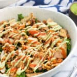 A large bowl of salad featuring buffalo chicken, tortilla strips, almonds, a buffalo sauce drizzle and avocado ranch dressing