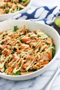Buffalo chicken kale salad is a filling and healthy lunch or dinner option that makes the most of leftover ingredients. Quickly massaged kale is topped with shredded buffalo chicken, almonds, crispy baked tortilla strips, and a homemade avocado ranch dressing for an ultra flavorful meal.