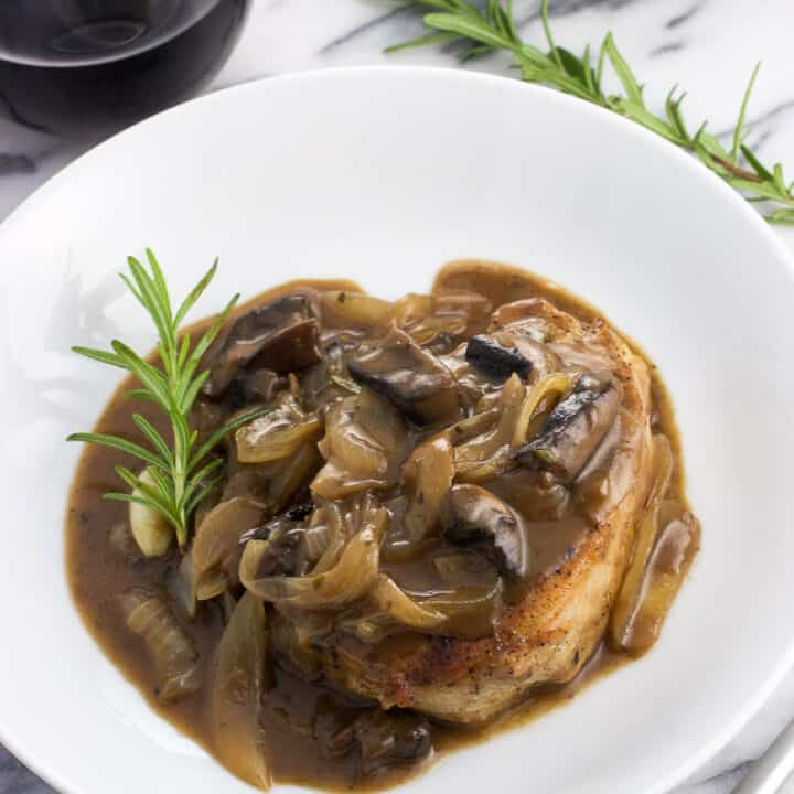 A balsamic pork chop on a dinner plate covered in sauce, mushrooms, and onions and garnished with a rosemary sprig. There's another rosemary sprig in the background along with a glass of wine