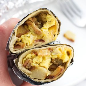Freezer breakfast burritos make a hearty breakfast loaded with eggs, breakfast potatoes, bacon, ham, and more. This easy make-ahead breakfast recipe is great to have on hand for busy days!
