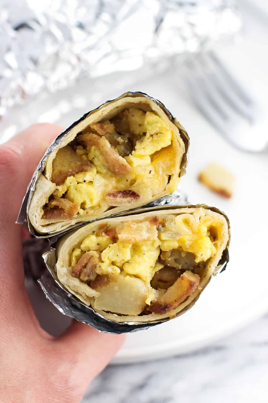A hand holding a foil-wrapped breakfast burrito cut in half to show the egg, potato, meat, and cheese filling
