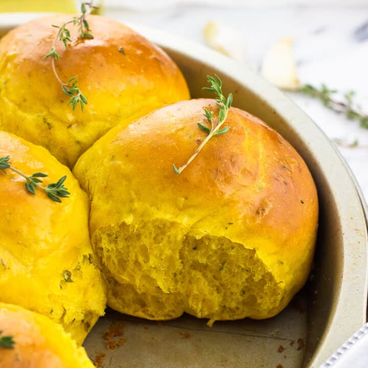 Pull-apart pumpkin rolls in a round cake pan topped with fresh thyme sprigs