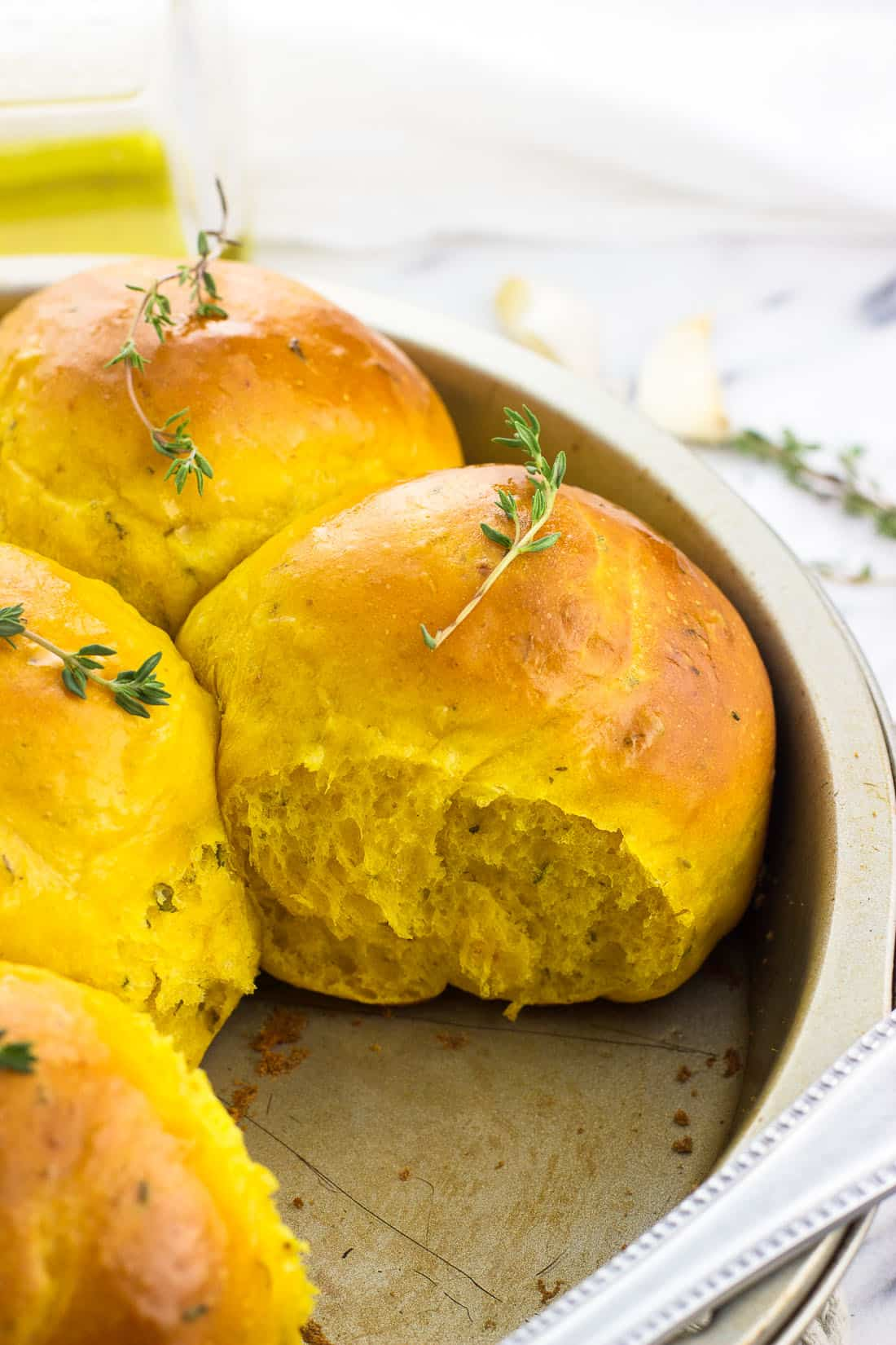 Garlic and herb pumpkin dinner rolls are perfectly flaky and fluffy, and make the best addition to a fall dinner. These pull-apart, yeast-based rolls are flavored with garlic and fresh herbs and are easy to make.