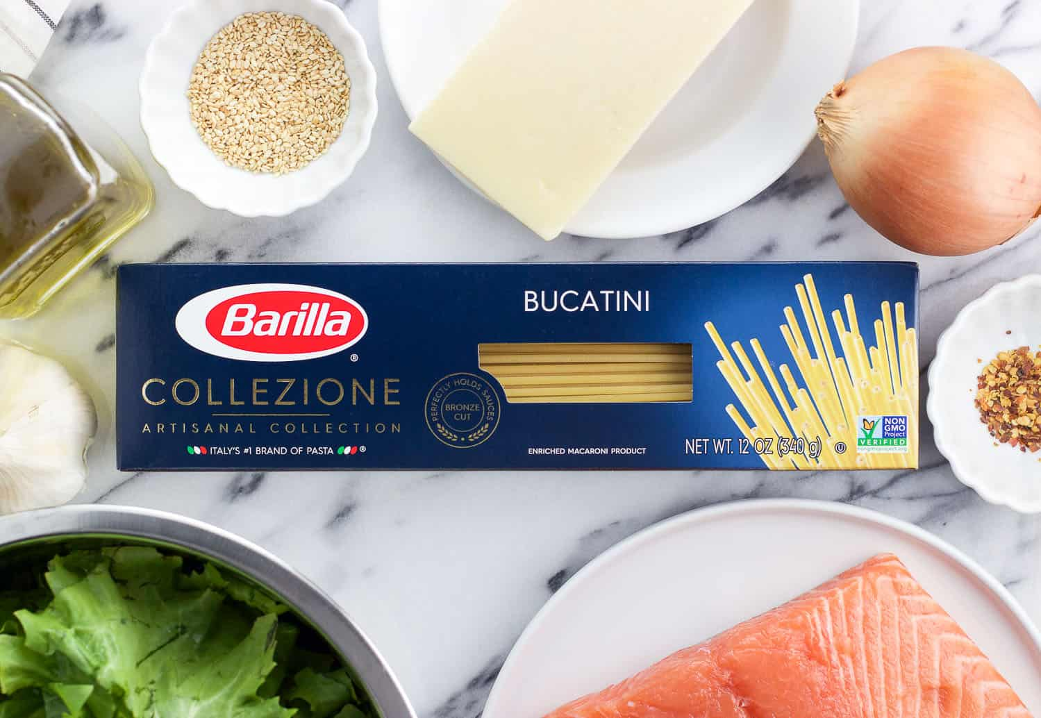 A box of Barilla Bucatini on a marble board surrounded by the rest of the recipe ingredients