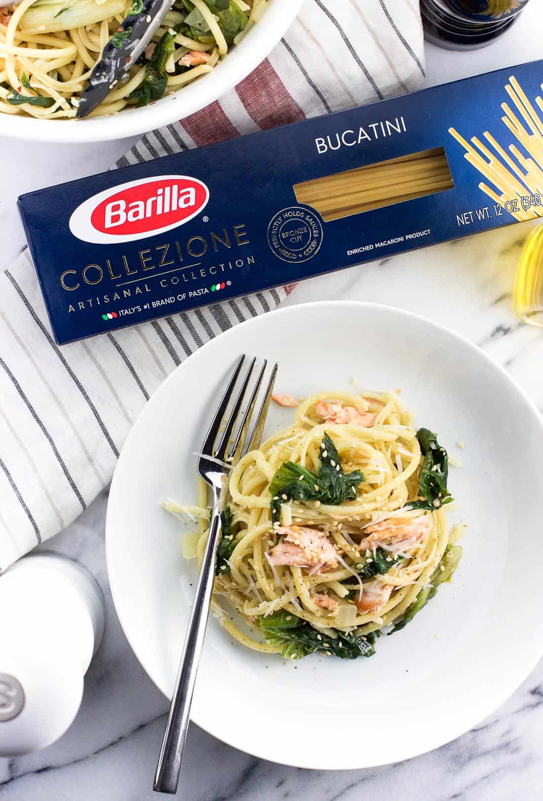 A plate of salmon pasta next to a package of Barilla Bucatini