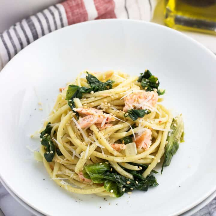 A serving of pasta, salmon, and escarole in a shallow dish