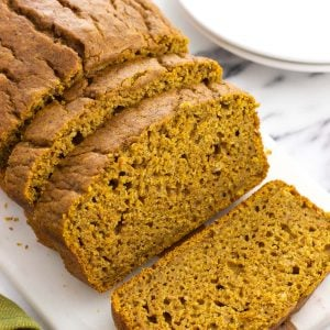 A loaf of half-sliced pumpkin bread on a serving tray.