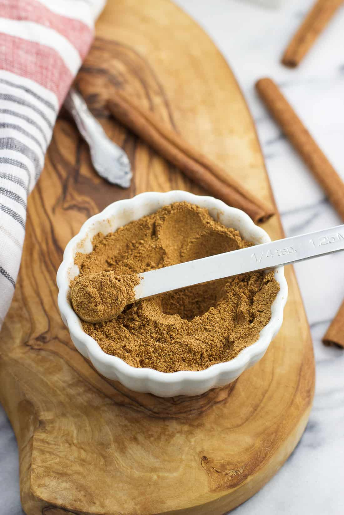 Stirred together chai spice with a quarter-teaspoon resting in the bowl with a heaping quantity of the spice mix in it