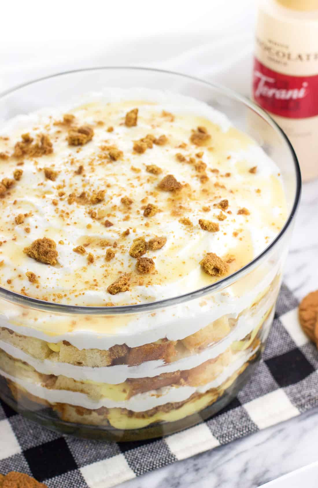 The pound cake trifle in a large trifle bowl with a bottle of Torani white chocolate syrup in the background