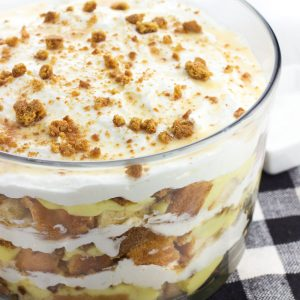 This pound cake trifle features salted honey, vanilla pudding, homemade stabilized (!) whipped cream, gingersnaps, and white chocolate sauce for a uniquely-flavored layered dessert. This make-ahead trifle is perfect for serving a crowd!