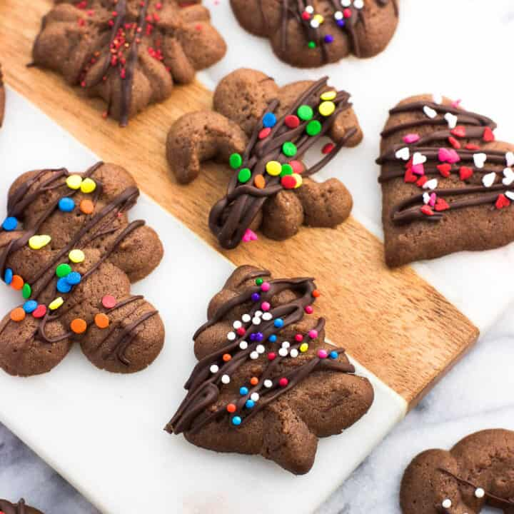 An assortment of chocolate spritz cookies drizzled with chocolate and sprinkles on a marble board.