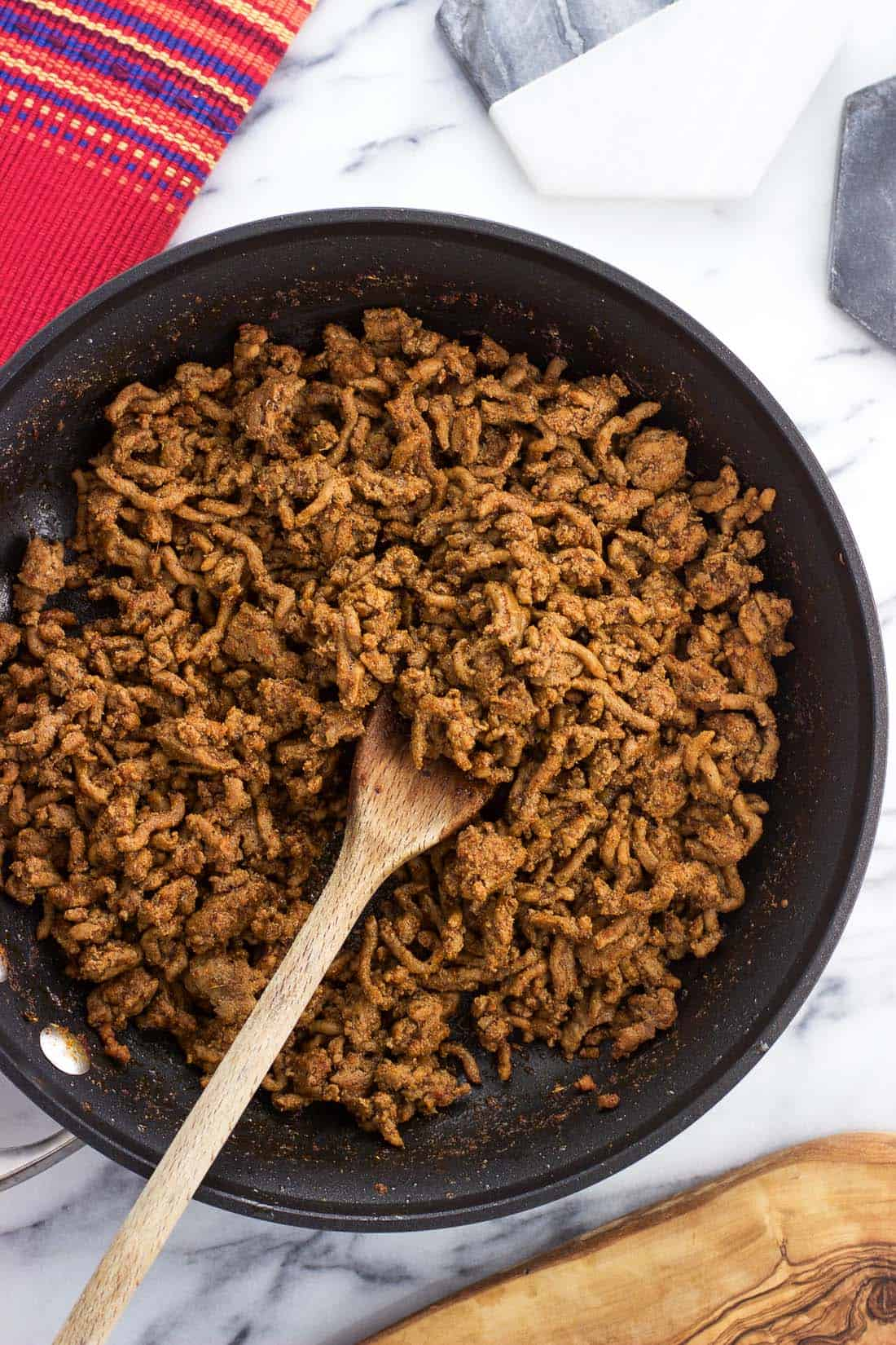 Cooked taco meat in a skillet with a wooden spoon.