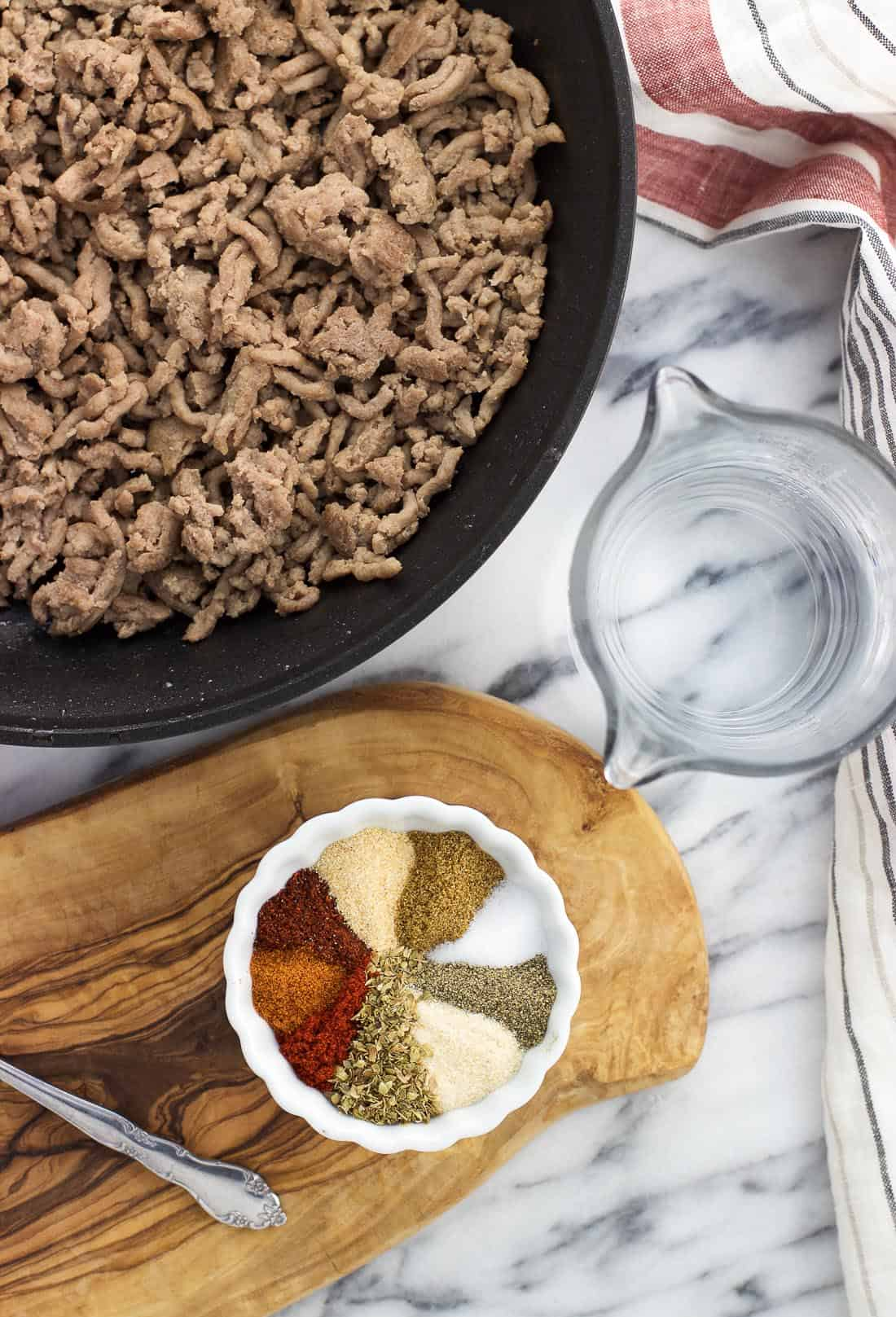 Crumbled cooked beef in a skillet next to a cup of water and a bowl of taco seasoning.
