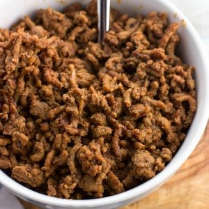 A bowl of taco meat with a spoon.