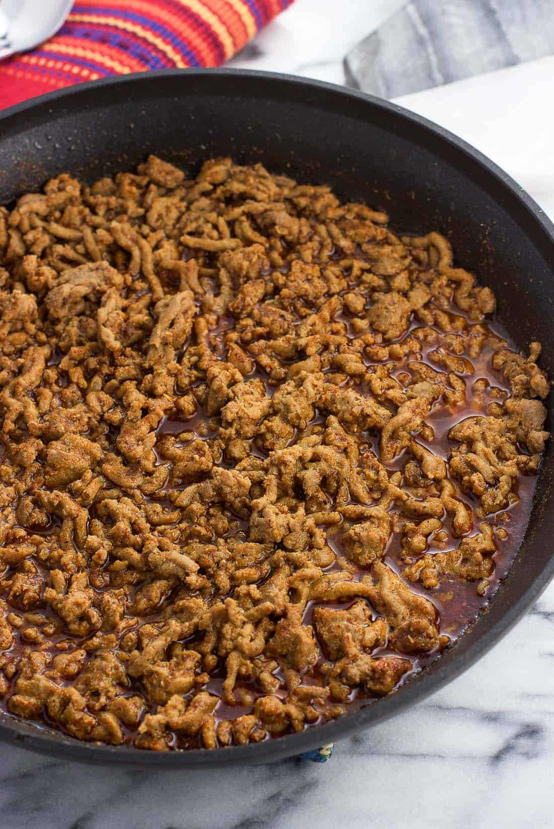 Seasoned taco meat in a skillet before the water has cooked down.