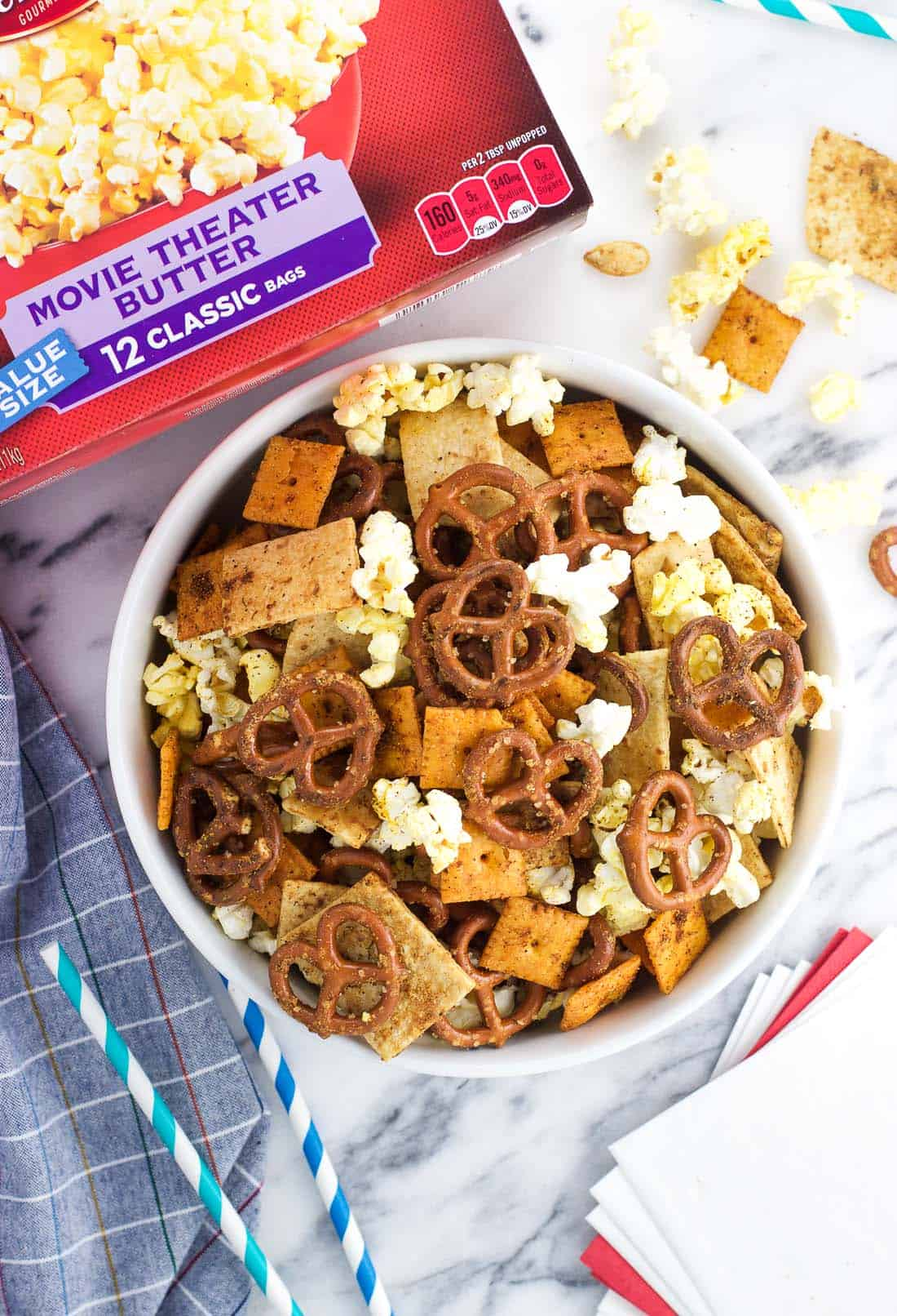 An overhead shot of a bowl of popcorn snack mix next to a box of popcorn