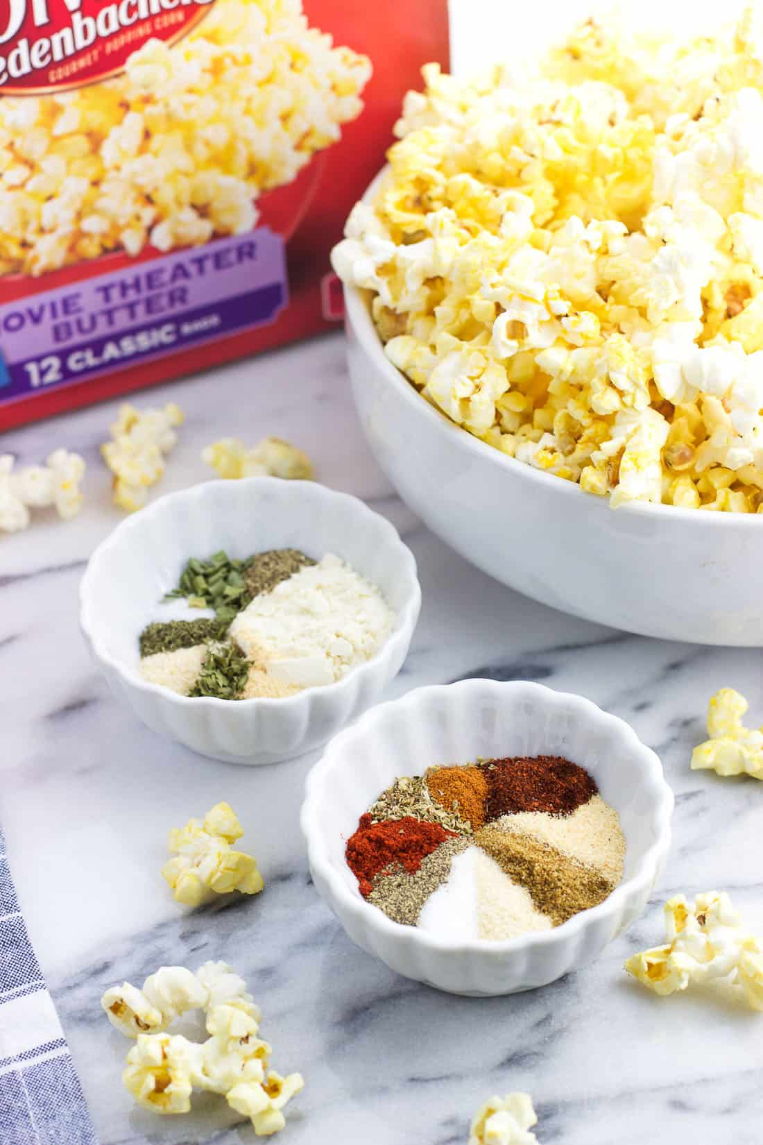 Two small bowls filled with spice mixes next to a large bowl of popped butter popcorn