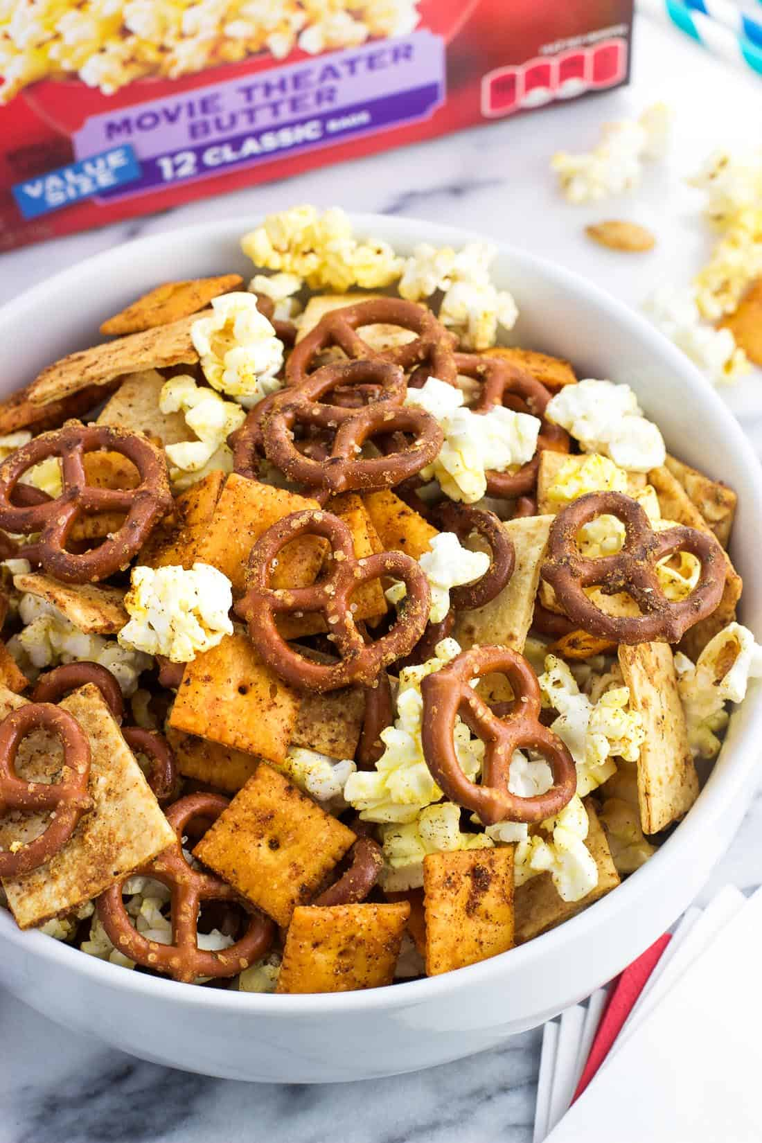 A bowl of popcorn snack mix next to a stack of napkins and paper straws for serving at a party