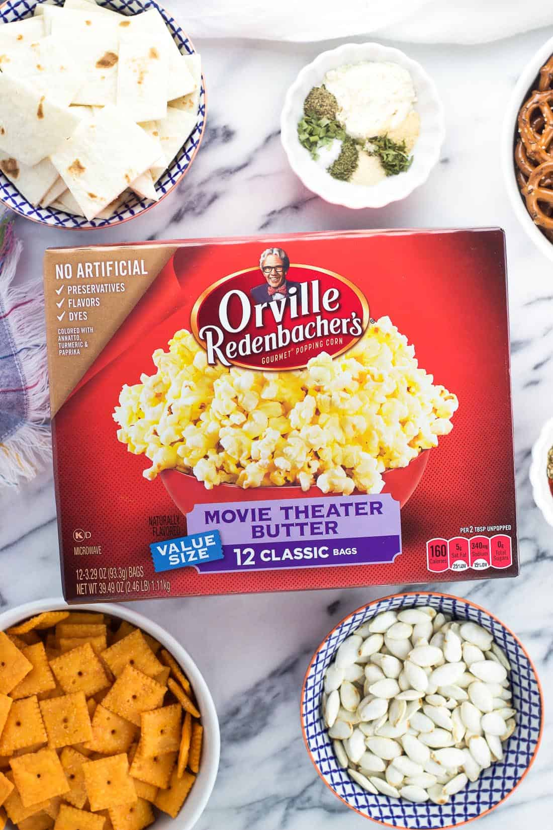 A box of popcorn on a marble board surrounded by the recipe ingredients in separate bowls