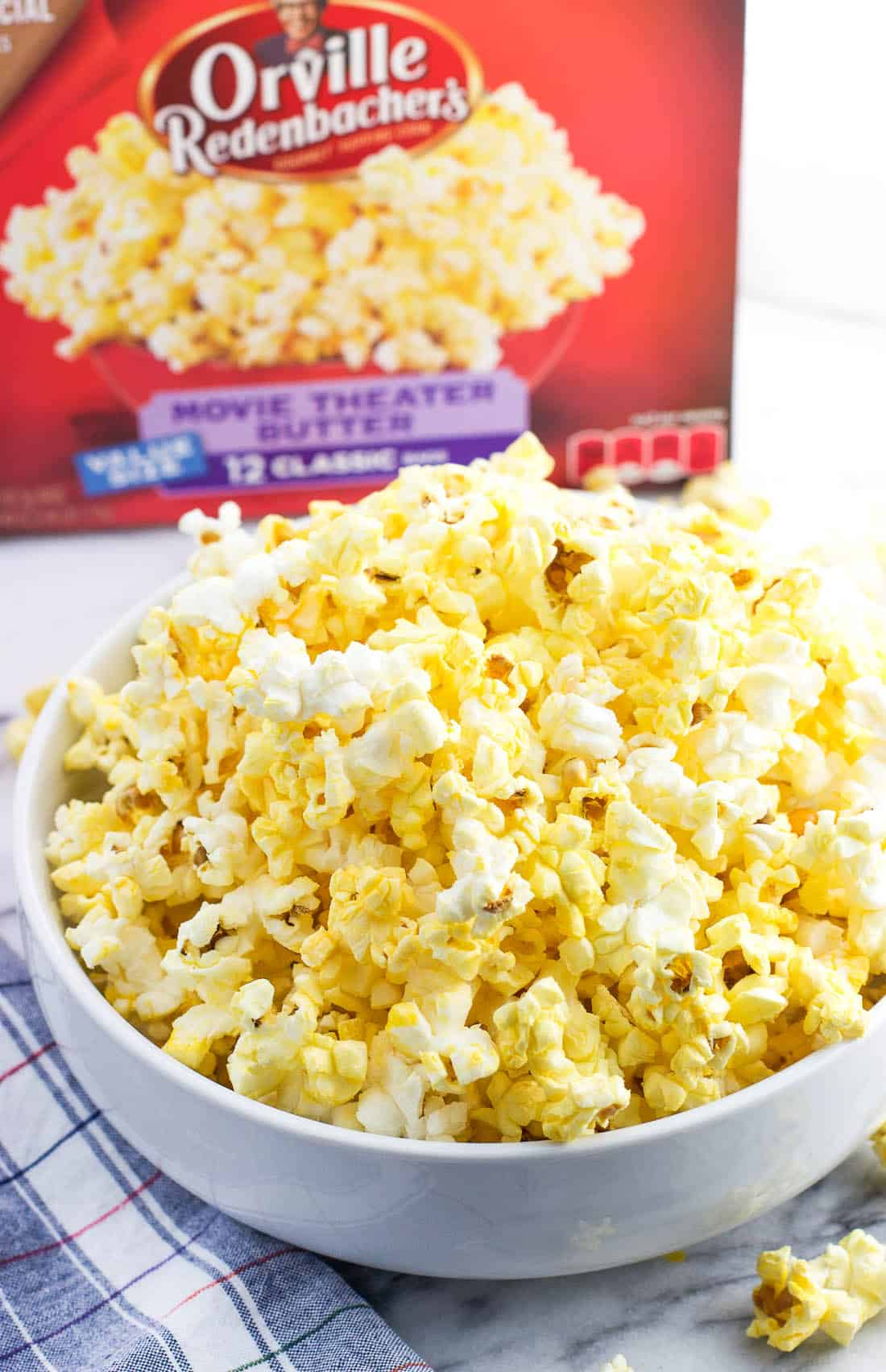 A bowl of popped popcorn next to the Orville Redenbacher's box