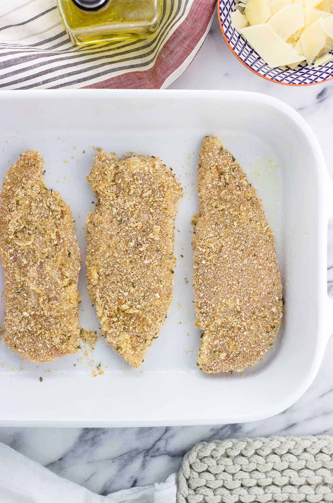 Chicken cutlets coated in breadcrumbs in a single layer in a large rectangular baking dish