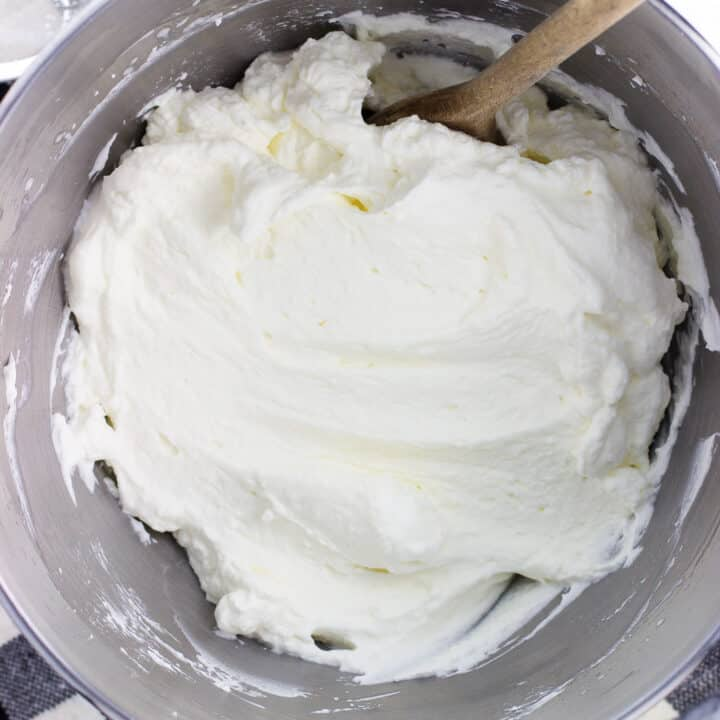 A stand mixer bowl of stabilized whipped cream with a wooden spoon.