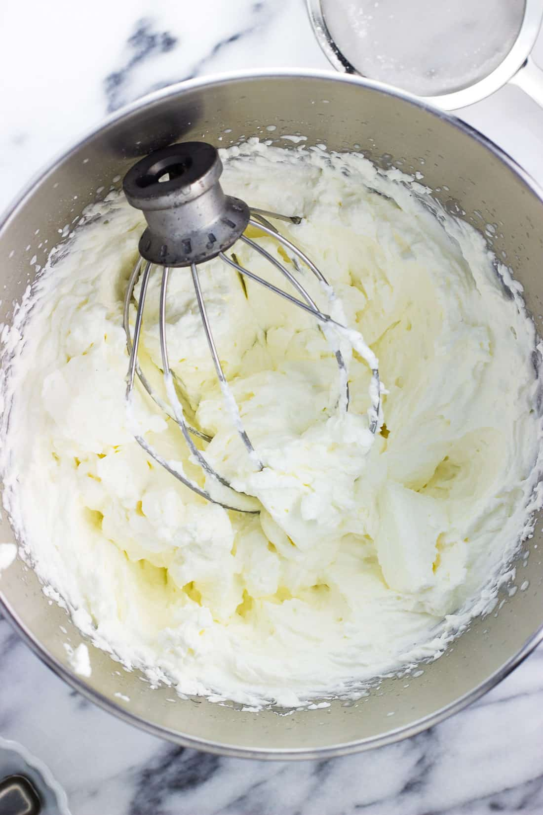 A metal stand mixer bowl of whipped cream with the beater attachment in it