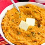 A bowl of mashed sweet potatoes topped with herbs and two pats of butter