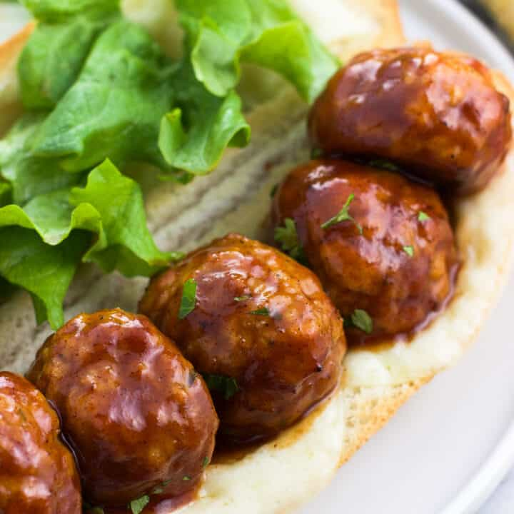 Five honey BBQ chicken meatballs open-face on a sub roll with melted cheese and lettuce