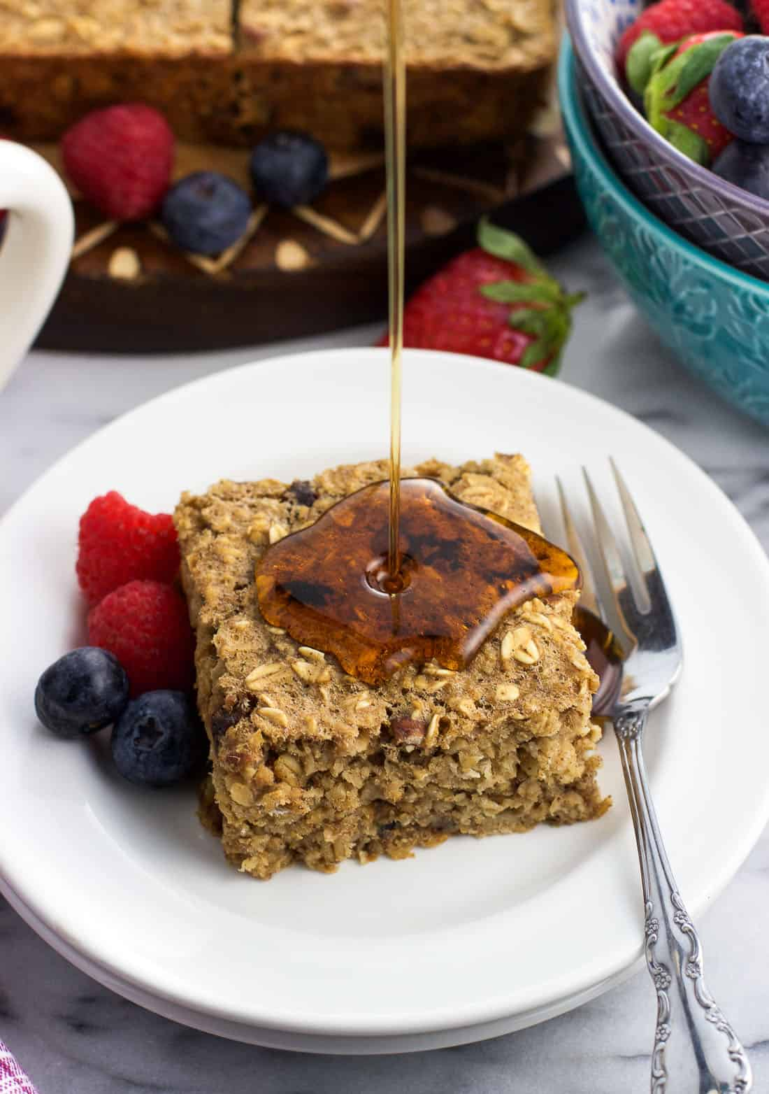 Fresh fruit and a baked oatmeal square on a plate being drizzled by maple syrup.