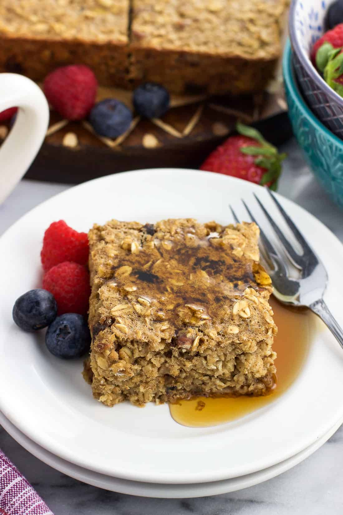 A maple syrup drizzled square of baked oatmeal on a plate with a fork and berries.