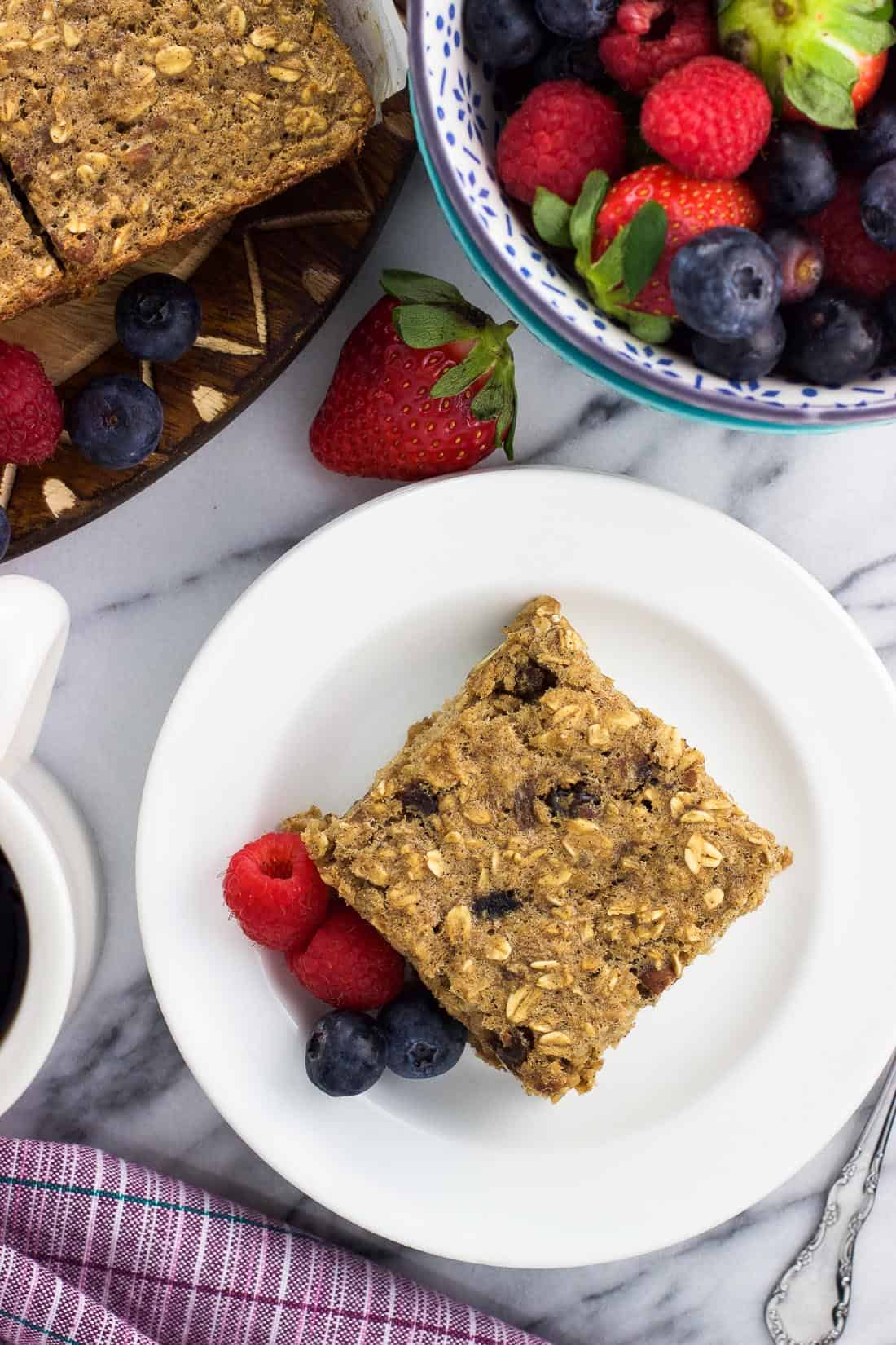 A piece of baked oatmeal on a plate next to a cup of coffee and a bowl of fruit.