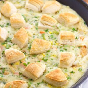 Fish pot pie topped with biscuit pieces in a skillet.