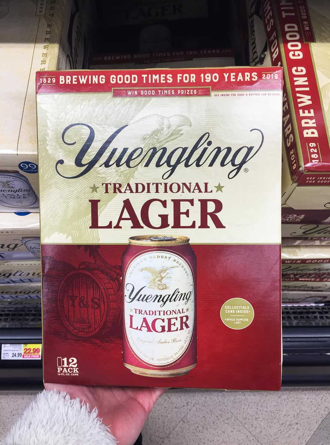 A hand holding a 12-pack of Yuengling Lager in the grocery store beer section