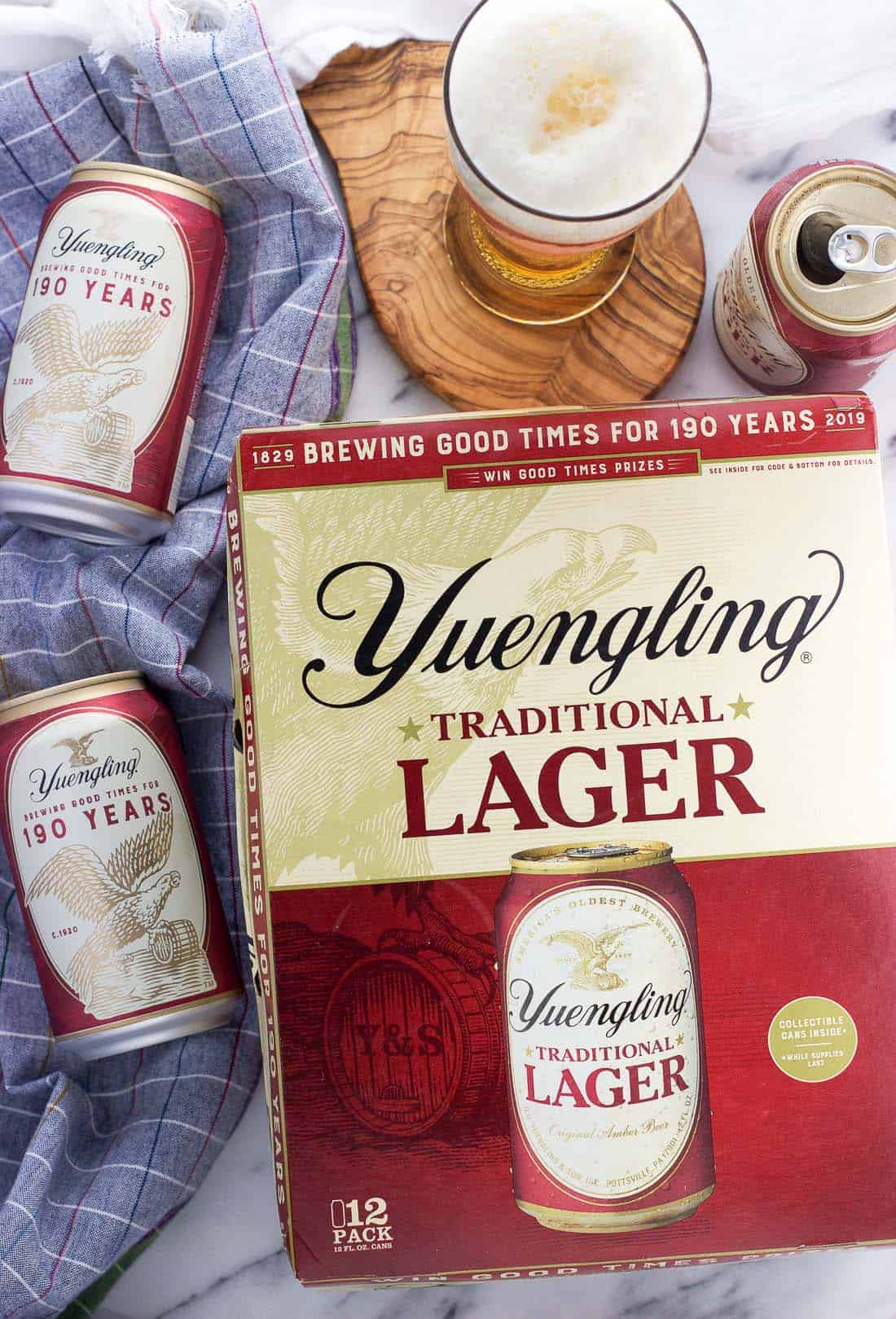 An overhead picture of a 12-pack of Yuengling Lager surrounded by cans of beer and a foamy-headed glass of beer