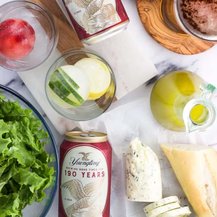 An overhead shot of frozen fruit slices in ice cubes, compound butter, vinaigrette dressing, a bowl of lettuce, two cans fo Yuengling lager and a poured glass of beer