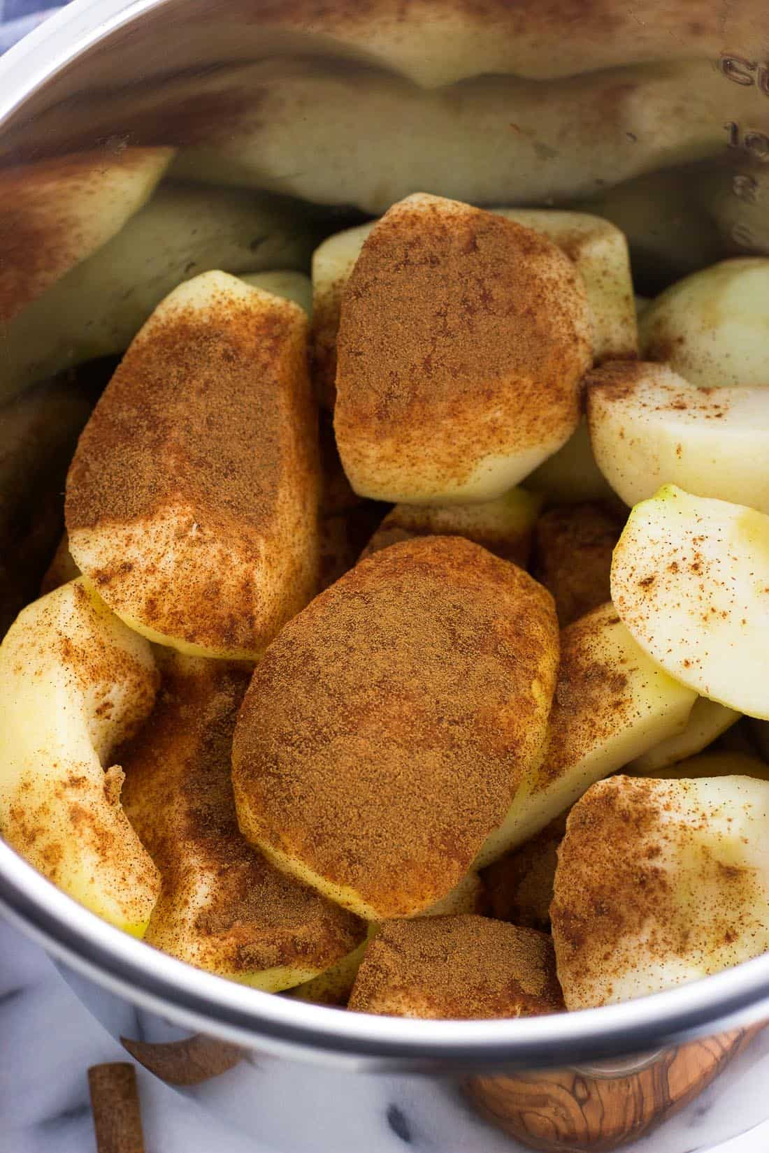 Peeled and quartered apples pre-cook in the Instant Pot, covered in ground cinnamon.