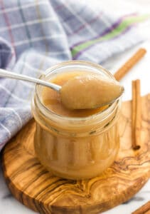 Applesauce in a jar with a spoon heaping full of applesauce resting on top.