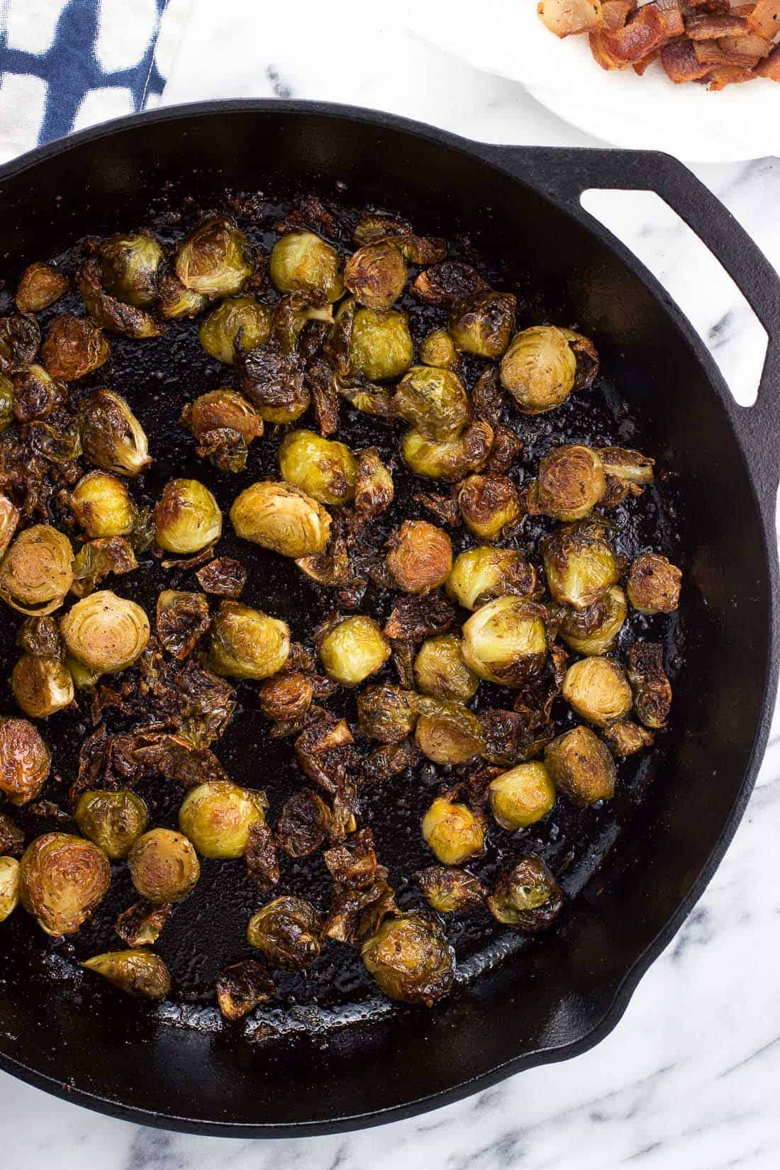An overhead view of roasted brussels sprouts in a cast iron skillet