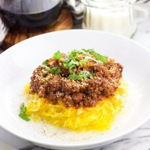 Spaghetti squash bolognese in a bowl with Pecorino Romano and basil on top as garnish