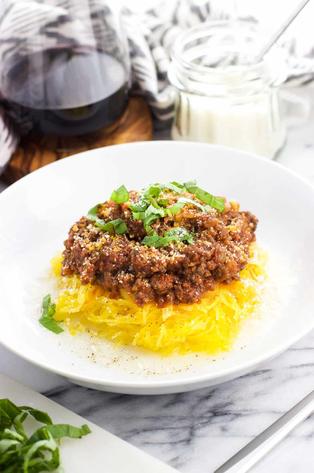 Bolognese sauce served over cooked spaghetti squash strands in a bowl with Pecorino Romano and basil on top as garnish, with extra cheese and a glass of red wine in the background
