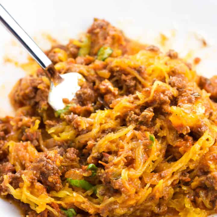 A serving of bolognese sauce and spaghetti squash all stirred up in a bowl with a fork