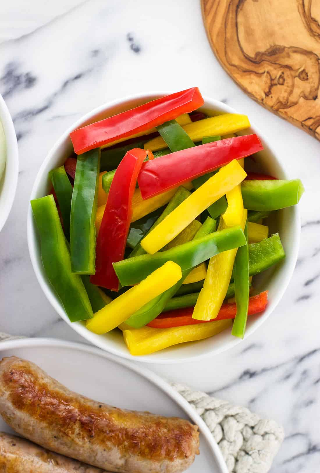 A variety of raw sliced peppers in a bowl next to browned Italian sausages.