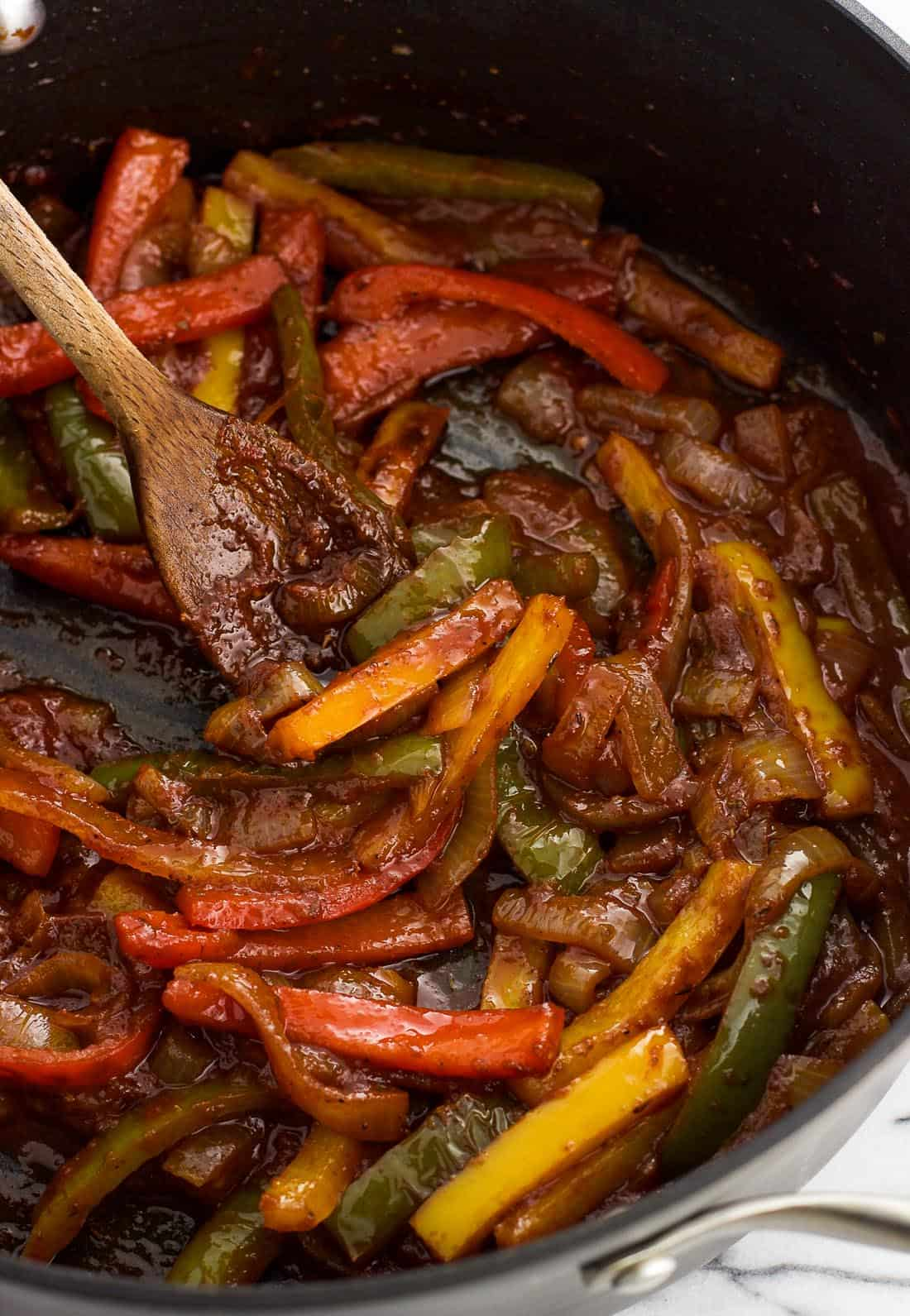 Sliced peppers and onions in a skillet with a thick tomato sauce