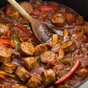 Italian sausage and peppers in sauce in a skillet with a wooden spoon